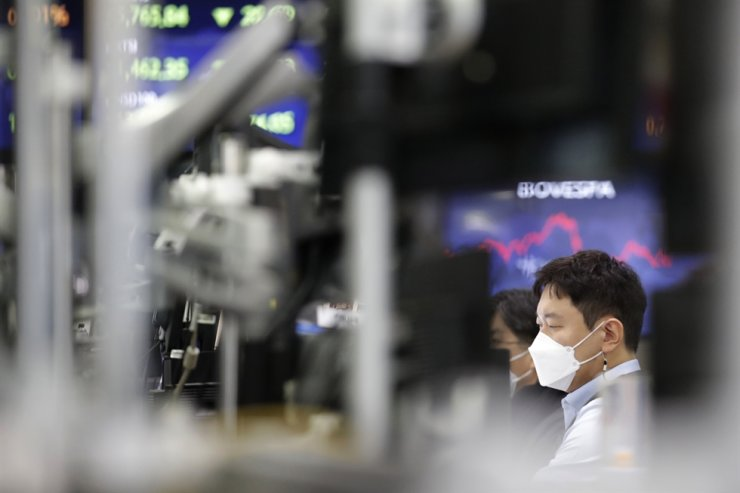 A currency trader watches computer monitors at the foreign exchange dealing room in Seoul, Feb. 18, 2021. AP