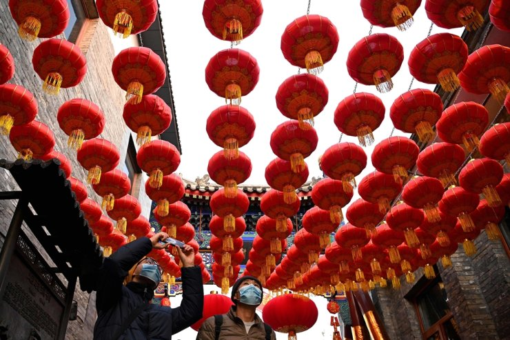 People walk under traditional Chinese lanterns along an alley in Beijing on February 9, 2021, ahead the biggest holiday of the year, the Lunar New Year, which ushers in the Year of the Ox on February 12. AFP-Yonhap