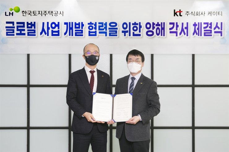 KT's head of global business Moon Sung-wook, left, poses with his counterpart at the Korea Land & Housing Corporation (LH), Lee Yong-sam, after the two companies signed an agreement to work together to build KT internet data centers overseas markets. / Courtesy of KT