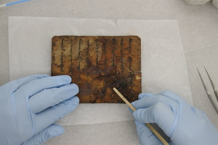 A conservation scientist cleans a Buddhist scripture written on bark from Mongolia at the Cultural Heritage Conservation Science Center. / Courtesy of National Research Institute of Cultural Heritage