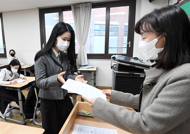 A high school senior receives a score card for the College Scholastic Ability Test (CSAT) at Hyesung Girls' High School in Seoul, Dec. 23, 2020. Korea Times file.