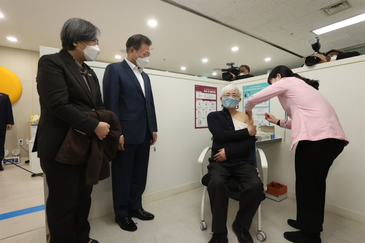 Dr. Kim Yoon-tae receives an injection of AstraZeneca's COVID-19 vaccine at a public health center in Seoul, Friday, as President Moon Jae-in and Korea Disease Control and Prevention Agency Commissioner Jeong Eun-kyeong watch the process. Yonhap