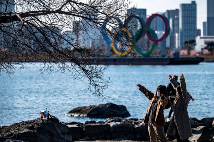 People pose for photos near the Olympic rings on display at the Odaiba waterfront in Tokyo on Feb. 24, 2021. AFP