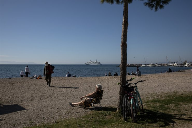 A woman enjoys a sunbath as a man wearing a protective face mask to curb the spread of coronavirus leaves a beach of Glyfada suburb, south of Athens, Saturday, Feb. 6, 2021. AP