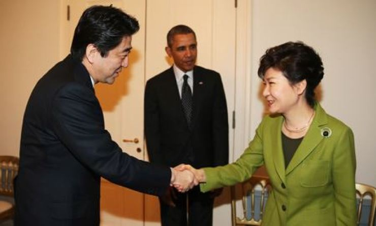 Former President Park Geun-hye, right, and former Japanese Prime Minister Shinzo Abe shake hands during a trilateral summit brokered by former U.S. President Barack Obama at the U.S. embassy in The Hague in this March 2014 photo. Korea Times file