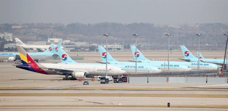 Airplanes of Korean Air and Asiana Airlines are parked at Incheon International Airport, March 31. Korean Air said Wednesday it plans to launch a merged entity with Asiana Airlines in 2024 after completing a takeover process next year. Yonhap