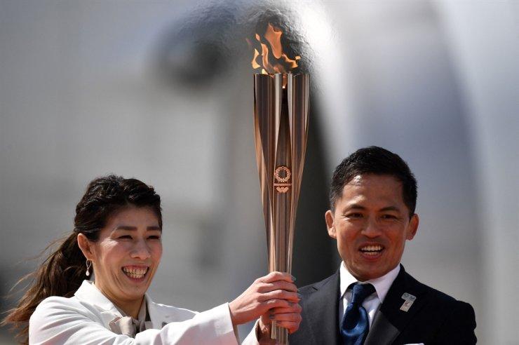Japanese three-time Olympic gold medalists Saori Yoshida, left, and Tadahiro Nomura hold the Tokyo 2020 Olympic Torch at the Japan Air Self-Defense Force Matsushima Base in Higashimatsushima, Miyagi, in this March 2020 file photo. AFP-Yonhap