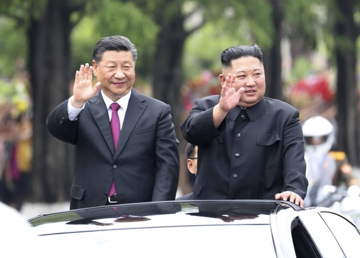 North Korean leader Kim Jong-un, right, and Chinese President Xi Jinping wave to people on a street in Pyongyang, June 20, 2019. Korea Times file