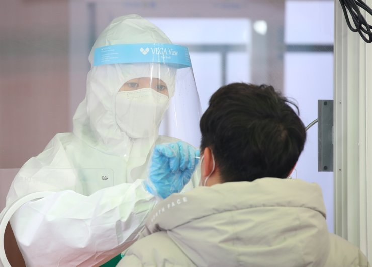 A man gets a COVID-19 testing at a makeshift testing site near Seoul Station, Tuesday. Yonhap
