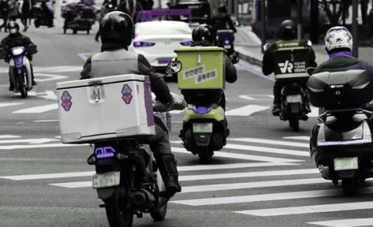 Delivery workers drive motorcycles equipped with top boxes on a street in Seoul in this file photo. Yonhap
