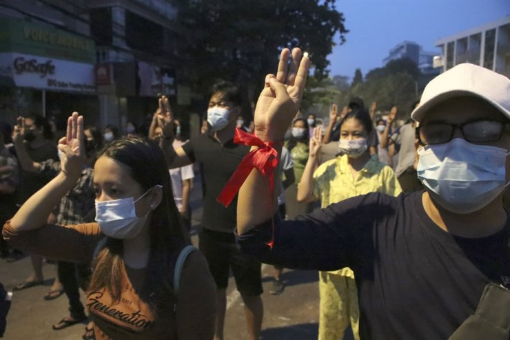 Anti-coup protesters flash three-fingered gesture, a symbol of resistance, during a rally outside their homes in downtown Yangon, Myanmar, Monday morning, March 22, 2021. Yonhap-AP Photo