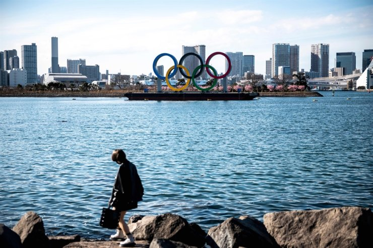 A woman walks in front of the Olympic rings on display at the Odaiba waterfront in Tokyo on Feb. 24, 2021. AFP