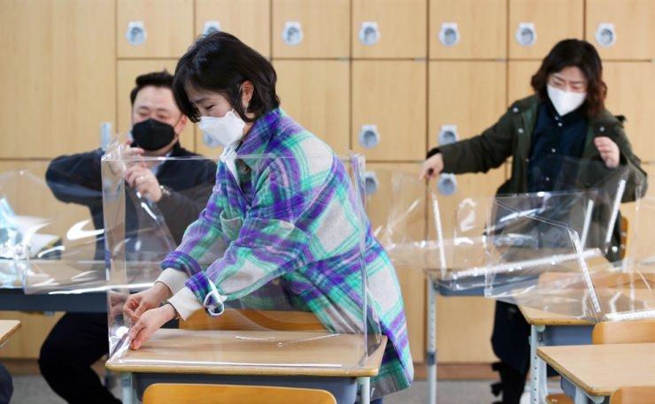 Teachers set up transparent screens on desks at a high school in Daegu, Feb. 23, ahead of the upcoming new school semester. Yonhap