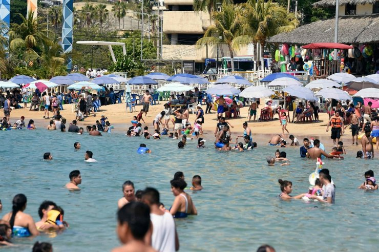 Tourists, mostly from Mexico City, enjoy Caleta Beach in the port of Acapulco, state of Guerrero, Mexico, on March 19, 2021 amid the COVID-19 pandemic. / AFP-Yonhap