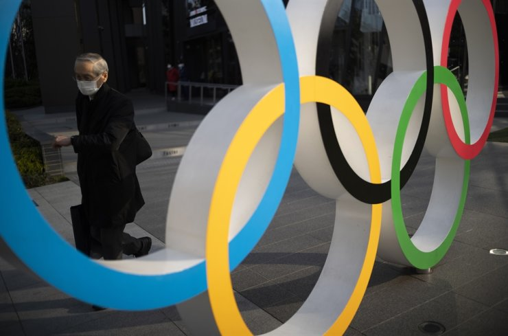A man walks by the Olympic rings installed at the Japan Olympic Museum in Tokyo on March 19, 2021. AP