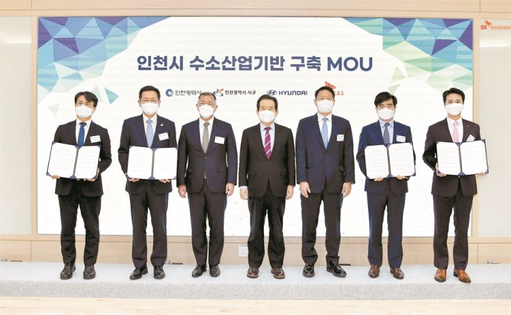 Prime Minister Chung Sye-kyun, center, poses with Hyundai Motor Group Chairman Chung Euisun, third from left, and SK Group Chairman Chey Tae-won, fifth from left, during a signing ceremony for an MOU on hydrogen related businesses between Hyundai Motor Group, SK Group and Incheon Metropolitan City, at SK Incheon Petrochem, Tuesday. From left are Incheon Seo-gu Office Head Lee Jae-hyun, Incheon Mayor Park Nam-choon, Chung, Prime Minister Chung, Chey, Hyundai Motor President Kong Young-woon and SK E&S CEO Choo Hyeong-wook. Courtesy of Hyundai Motor Group