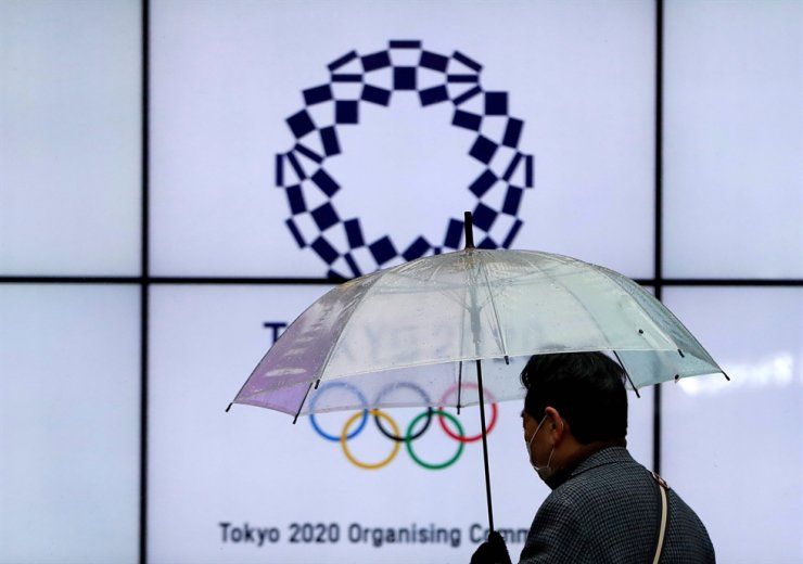 A man wearing a protective face mask walks past in front of a display showing the logo of Tokyo 2020 Olympic Games that have been postponed to 2021 due to the coronavirus disease (COVID-19) outbreak, in Tokyo, Jan. 23, 2021. Reuters