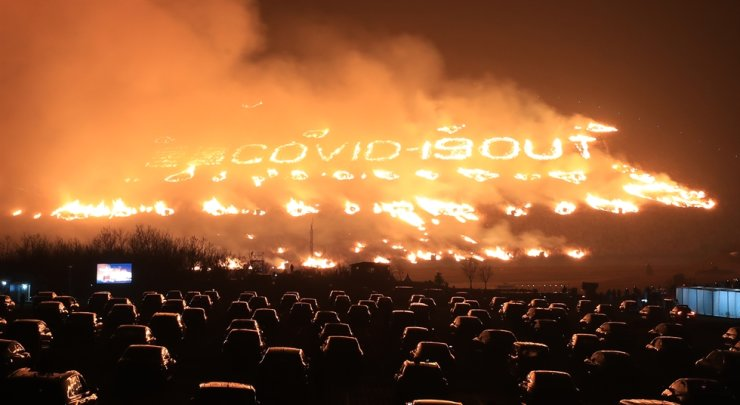 One of 'oreums,' or hills, in Jeju Island's Aewol District is on fire during the island's traditional fire festival on Mar. 13, with flames prepared to shape in letters that read 'COVID-19 OUT' to wish the global pandemic's end. Visitors to the oreum watch the festival in their cars. Yonhap