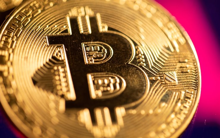 A representation of virtual currency Bitcoin is seen in front of a stock graph in this illustration taken March 15, 2021. Reuters
