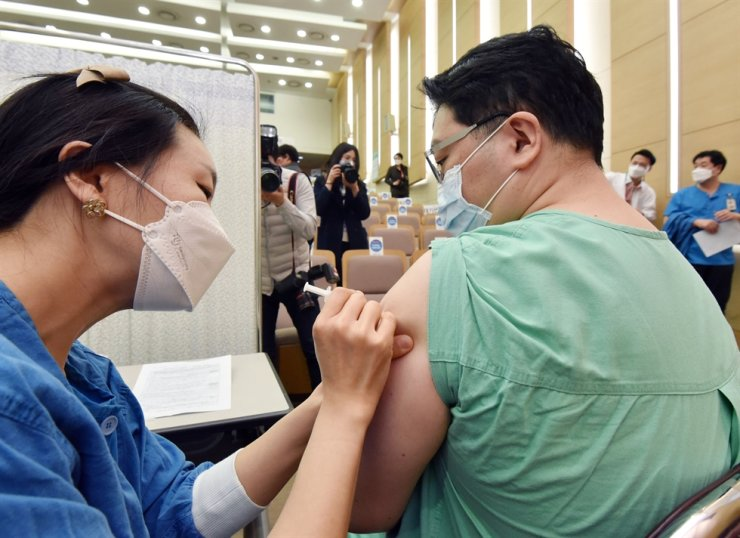 A medical worker receives the first shot of AstraZeneca's two-dose COVID-19 vaccine at Seoul National University Hospital, Thursday. Yonhap