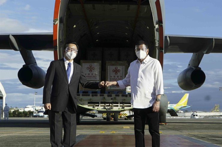 In this photo provided by the Malacanang Presidential Photographers Division, Philippine President Rodrigo Duterte, right, poses with Chinese Ambassador to the Philippines Huang Xilian, second from left, as they stand in front of a military place carrying Sinovac vaccines from China at the Villamor Air Base in Manila, Sunday Feb. 28, 2021. AP