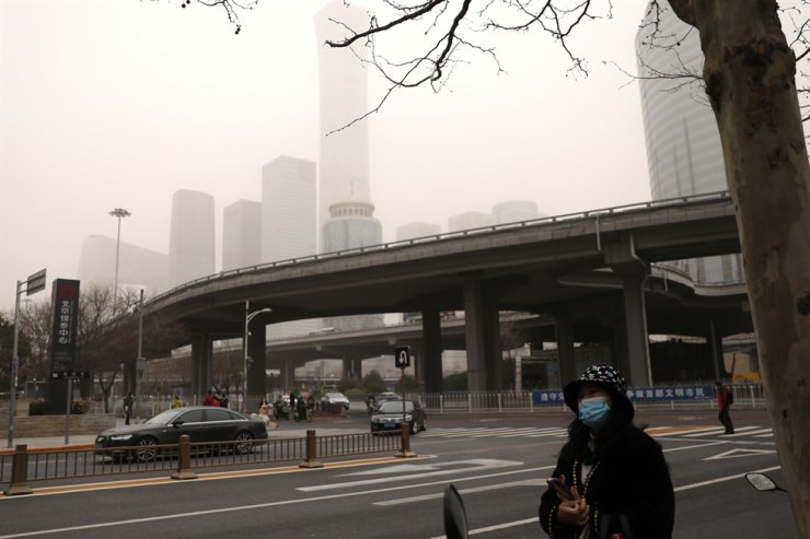 A woman wearing a face mask stands on a street in Beijing's Central Business District, China, March 15, 2021. Reuters