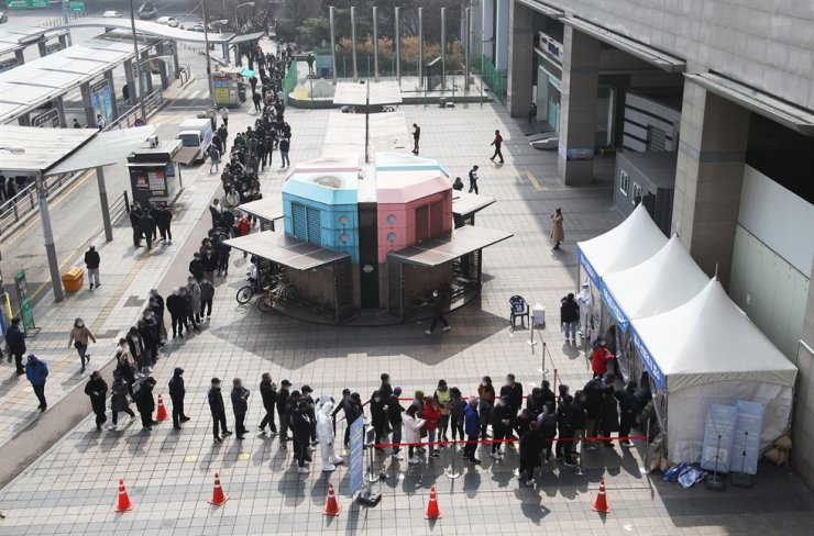 A temporary COVID-19 testing center in front of Suwon Station in Gyeonggi Province is crowded, Sunday, following the recent administrative order from Gyeonggi Provincial Government for all foreign workers in the area to take a COVID-19 test. Yonhap