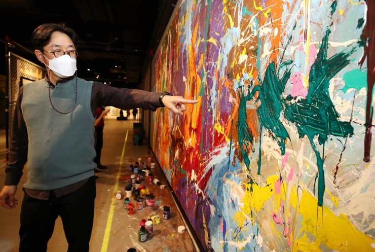 Kang Wook, CEO of Contents Creator of Culture (CCOC), a co-organizer for the exhibition 'Street Noise' held in Seoul's Lotte World Mall, points to the vandalized work of the American graffiti artist JonOne, March 28. Yonhap