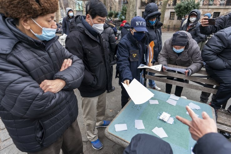 In this March 17, 2021, file photo, Detective Suk H Too, second from right, with the New York Police Department Community Affairs Rapid Response Unit hands out fliers with information on how to report hate crimes to residents while on a community outreach patrol in the Chinatown neighborhood of New York. AP-Yonhap