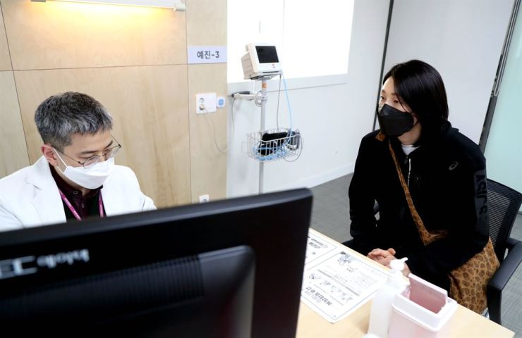 Volleyball star Kim Yeon-koung speaks to a doctor before getting the COVID-19 vaccine at the National Medical Center in central Seoul, Thursday. Yonhap