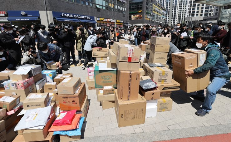 Delivery workers stack parcels at the entrance of a large apartment complex in Seoul's Gangdong District, Wednesday, as they decided to refuse door-to-door services in protest of the resident representatives' ban on the workers from driving on aboveground roads within the complex. Yonhap