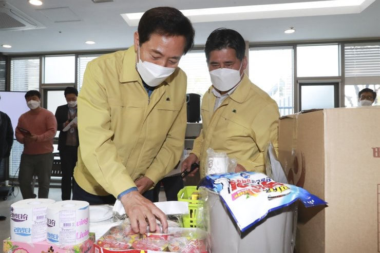 Seoul Mayor Oh Se-hoon, left, on April 10 checks foods and others provided at a temporary COVID-19 recovery center prepared by the city at Seoul Youth Hostel in Jung District, where those with not severe symptoms of the disease stay. Yonhap
