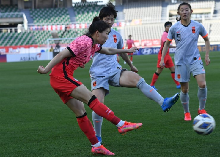 South Korea's women's national football team midfielder Kang Chae-rim, left, attempts a cross during the Tokyo Olympic qualification match against China at the Goyang Stadium in Gyeonggi Province, Thursday. South Korea lost the match 2-1. / Yonhap