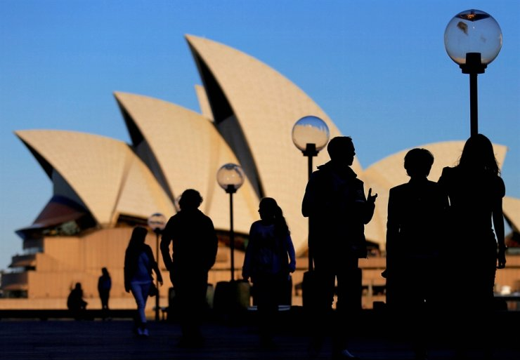 People are silhouetted against the Sydney Opera House at sunset in Australia, Nov. 2, 2016. Australia's government said Wednesday that it cancelled 'Belt and Road' infrastructure deals with China. Reuters