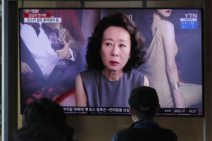 People watch a TV screen showing a news program reporting Korean actress Youn Yuh-jung received the Oscar for best supporting actress for her performance in 'Minari,' at Seoul Railway Station in Seoul, April 26 (KST). AP