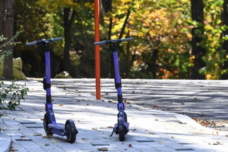 Two electric scooters are parked in the middle of a sidewalk on a university campus in Seoul in this Nov. 3, 2020 photo. Korea Times photo by Lee Han-ho