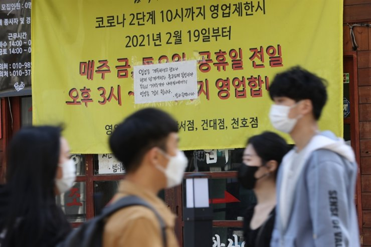 People walk past a closed bar in Mapo District, Seoul, April 9, while the attached notice reads that it is closed due to a ban imposed on entertainment facilities in the greater Seoul area. Yonhap