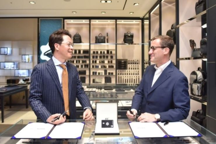 Lotte Card CEO Cho Jwa-jin, left, talks with Montblanc Korea's managing director Eric Eder during a signing ceremony for the two companies' partnership at Lotte Department Store's main branch in central Seoul, Tuesday. Lotte Card will issue special limited-edition cards in May to 1,906 customers, representing the luxury brand's founding year in 1906. Courtesy of Lotte Card