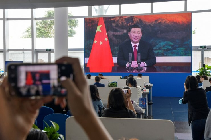 A journalist takes a photo of a screen showing a live image of Chinese President Xi Jinping delivering a speech at the opening of the Boao Forum for Asia (BFA) Annual Conference 2021 in Boao, Hainan province, April 20. AFP-Yonhap