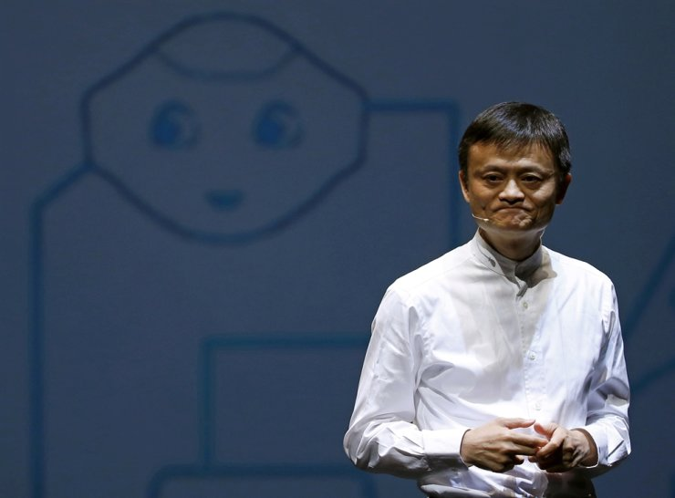 Jack Ma, founder and executive chairman of China's Alibaba Group, speaks in front of a picture of SoftBank's human-like robot named 'pepper' during a news conference in Chiba, Japan, June 18, 2015. Alibaba was fined 18.3 billion yuan ($2.8 billion) by Chinese regulators Saturday for anti-competitive tactics. Reuters