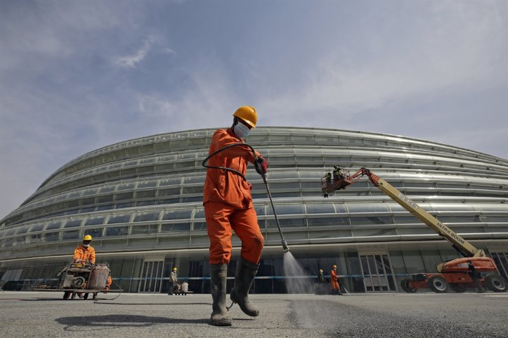 Workers fix the surface of a road outside the newly completed National Speed Skating Oval ahead of the 2022 Beijing Winter Olympics test events in Beijing, March 31. AP