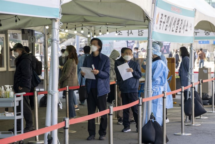People stand in line at a makeshift coronavirus testing site in front of Seoul Station, Thursday. Yonhap