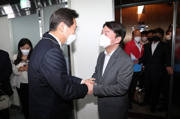 Oh Se-hoon, left, of the main opposition People Power Party (PPP), shakes hands with Ahn Cheol-soo, the head of the minor opposition People's Party, at the PPP's headquarters on Yeouido, Seoul, Thursday, after Oh's election as the new Seoul mayor in Wednesday's by-election was confirmed. Korea Times photo by Oh Dae-geun