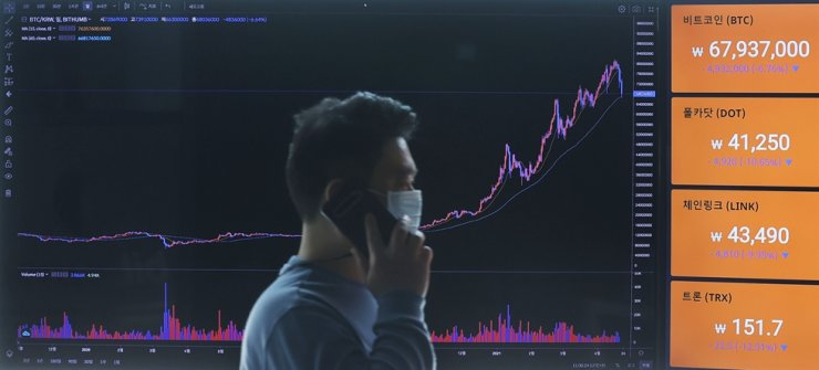 An official at Bithumb, a Seoul-based cryptocurrency exchange, looks at digital asset prices displayed on an electronic board in its Seoul office, Tuesday. Yonhap