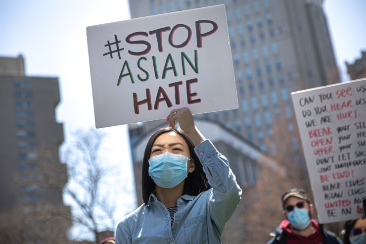 A woman holds a placard as she participates in a 'Stop Asian Hate' rally at Columbus Park in New York, Saturday. Reuters-Yonhap