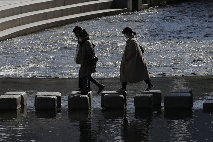 Visitors wearing face masks as a precaution against the coronavirus cross a stream in Seoul, April. AP