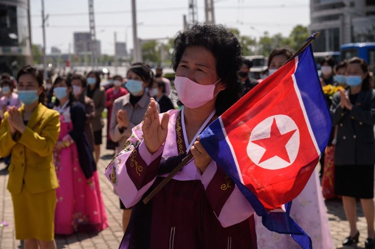 A woman wearing traditional dress and holding a North Korean flag watches a performance celebrating the 89th anniversary of the founding of the Korean People's Revolutionary Army, a precursor to the Korean People's Army, in Changjon Street in Pyongyang, April 25. A United Nations committee called on North Korea to provide an explanation on reported cases of human rights violations and to report any progress. AFP-Yonhap