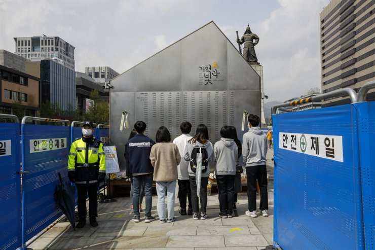People watch names of the victims of Sewol ferry disaster that are inscribed on a monument at Gwanghwamun Square in Seoul's Jongno District, Friday. Korea Times photo by Shim Hyun-chul