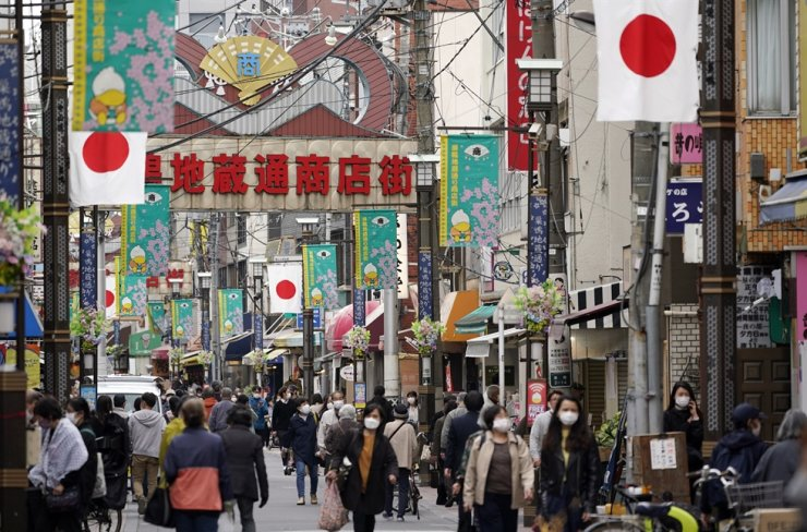 People walk on a shopping street in Sugamo district in Tokyo, April 9. The government adopted tougher measures against the coronavirus Monday. EPA
