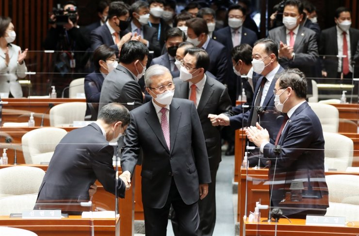 Kim Chong-in, center, the interim head of the main opposition People Power Party, gets applause as he enters a party meeting at the National Assembly in Seoul, Thursday, a day after the party won a landslide victory in the Seoul and Busan mayoral by-elections. Yonhap